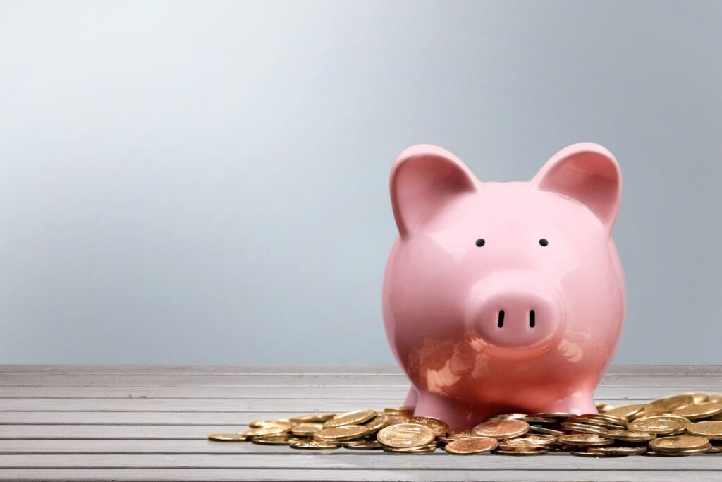 Imagem de cofre no formato de porquinho na cor rosa, moedas douradas em volta. Acumular milhas e tenha mais benefícios smiles.