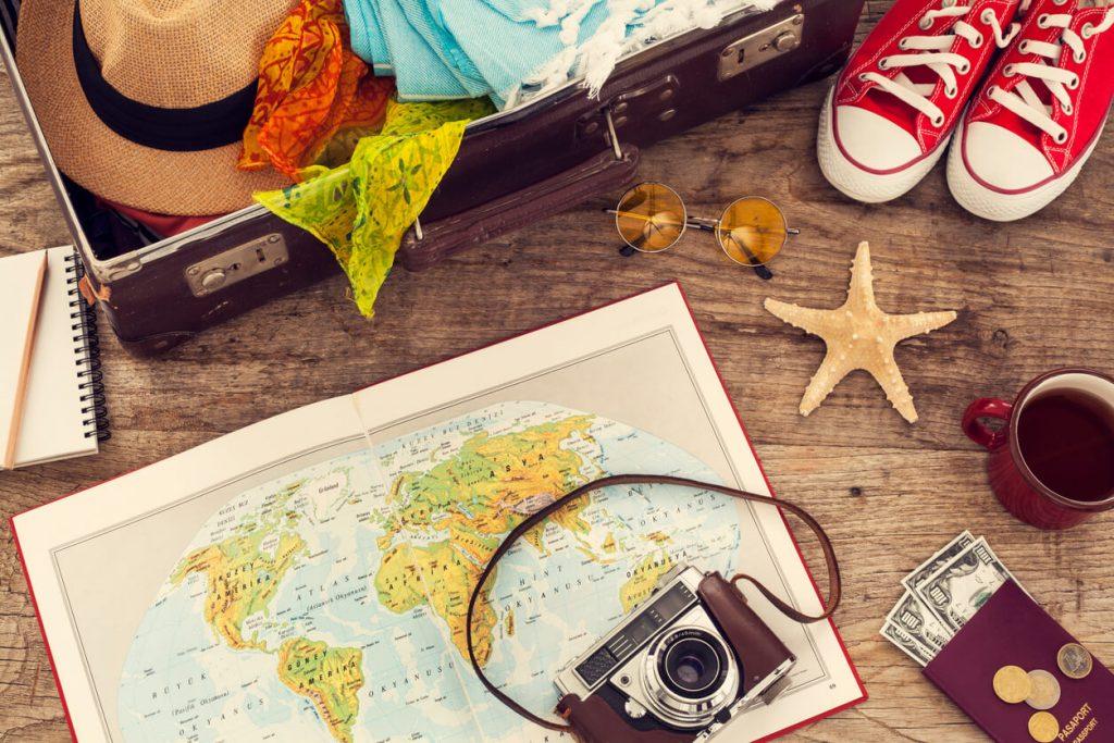 Imagem de itens de viagem, como máquina fotográfica, mapa, mala e roupas.