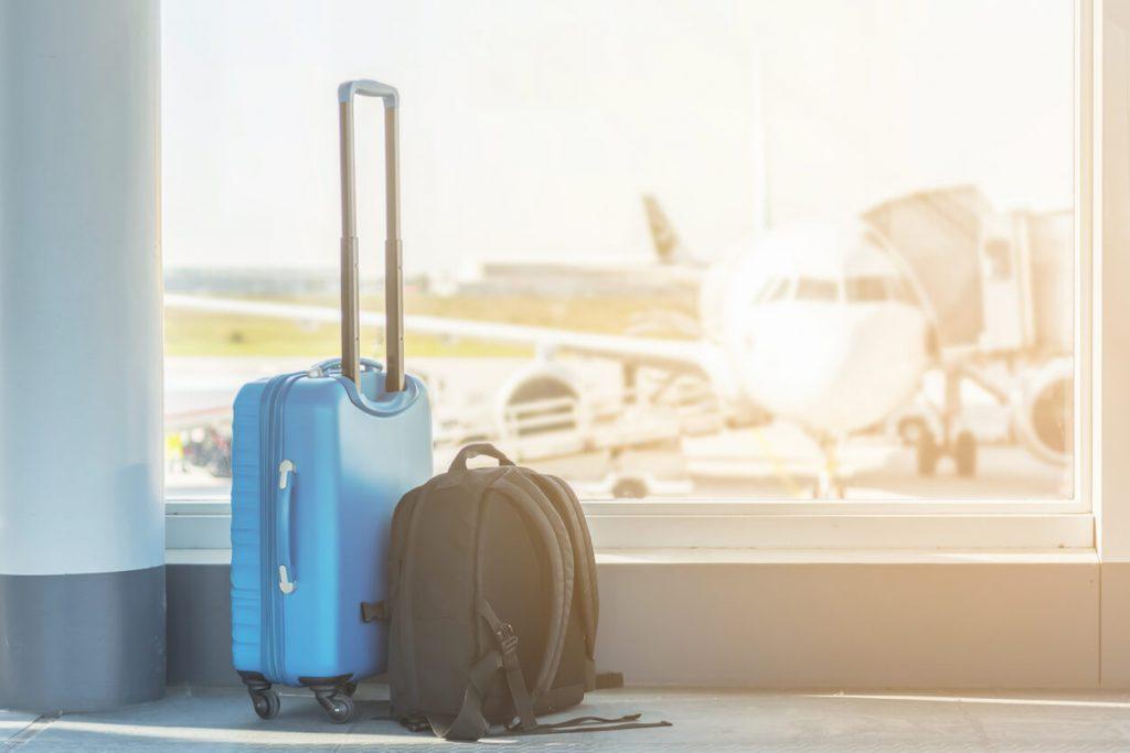 Imagem de mala e mochila de viagem no aeroporto de pessoas que viajam e não deixam milhas expirar.