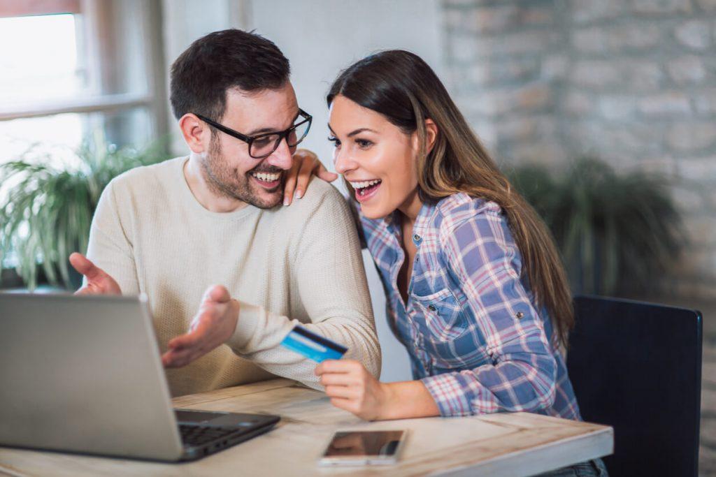 Imagem de casal feliz realizando compras online