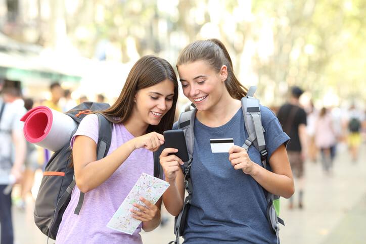 Imagem mostra amigas escolhendo destino de viagem para comprar no cartão de crédito