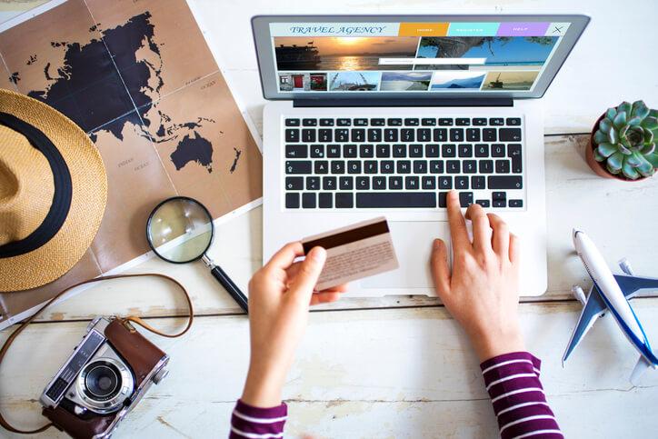 Imagem mostra pessoa comprando passagem no cartão de crédito pelo computador