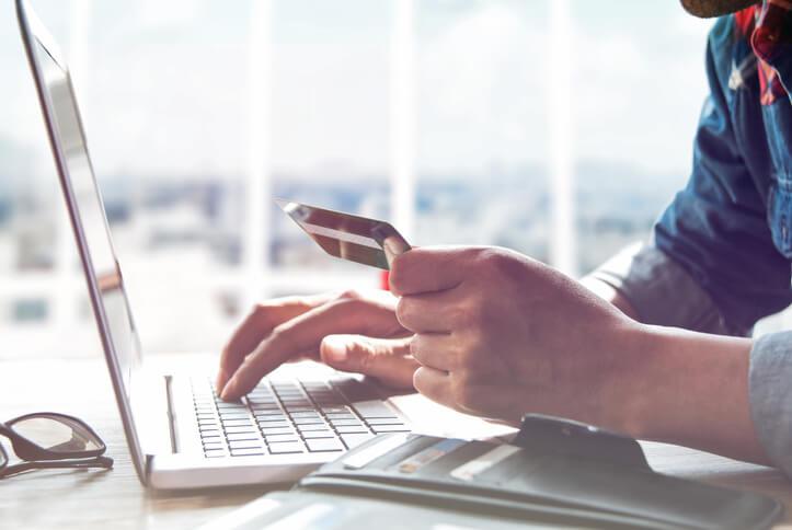 Imagem de homem usando cartão de crédito para realizar compras online para acumular pontos qualificáveis smiles