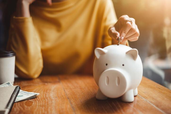 Imagem mostra pessoa colocando moeda no porquinho de economias que foram acumuladas de pontos de milhas vendidas
