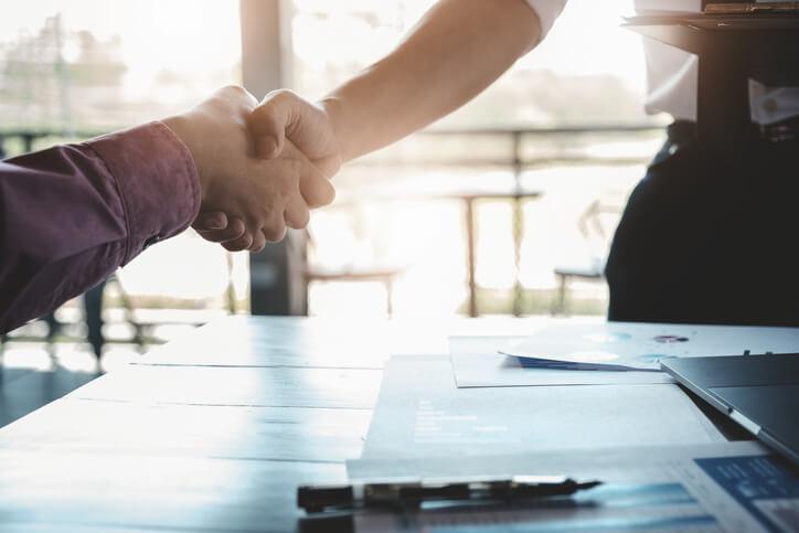 Imagem mostra aperto de mãos entre duas pessoas que falam sobre vender milhas com segurança e dicas para encontrar empresa confiável