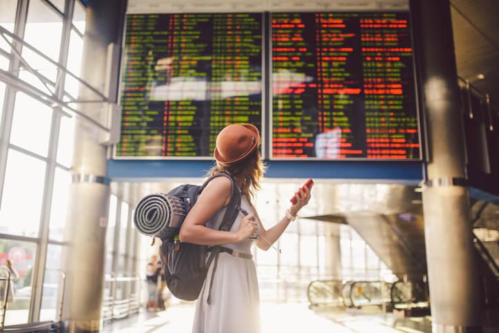 Moça olhando painel e analisando as companhias aéreas internacionais que mais dão retorno em milhas.