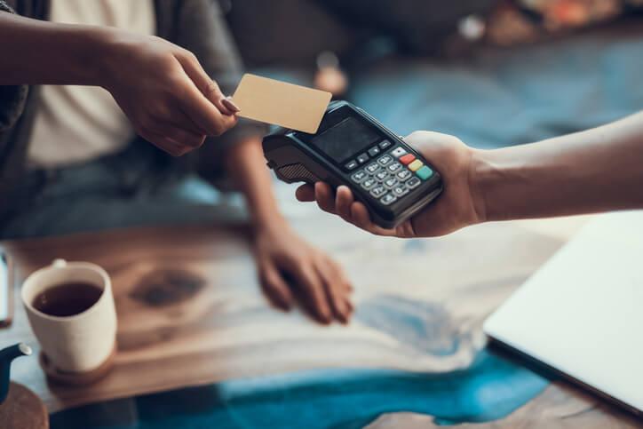 Imagem mostra pessoa passando compra no cartão