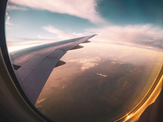 Imagem mostra alguém de dentro do avião tirando foto do céu