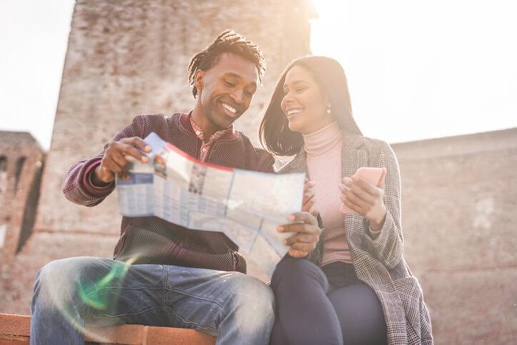 Imagem de casal procurando destinos de viagens internacionais com milhas no mapa