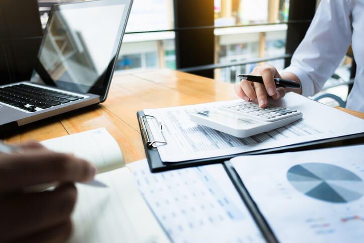 Imagem mostra mão de pessoa fazendo cálculos em calculadora depois de receber dicas para duplicar milhas em um mês