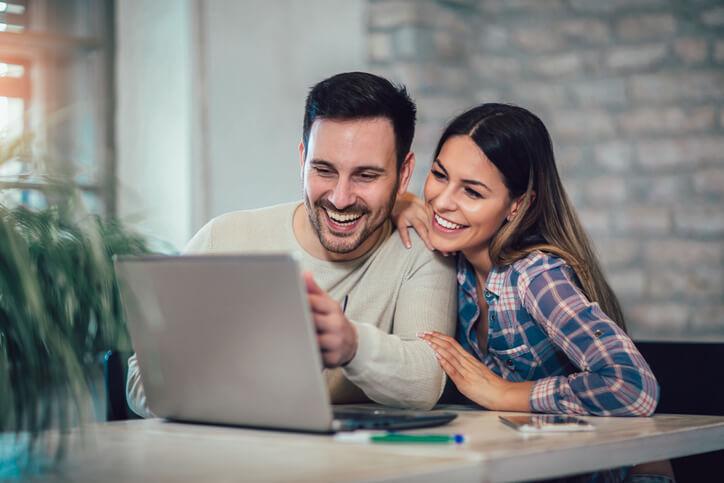 Imagem de casal feliz usando o computador para fazer compras e acumular pontos e saber quanto vale milhas em dinheiro.