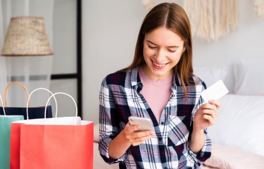 Mulher segurando cartão de crédito fazendo compras para ganhar milhas em casa.
