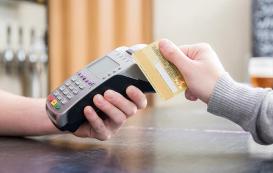 Mão segurando máquina de cartão de crédito para realizar pagamento e começar a ganhar milhas.