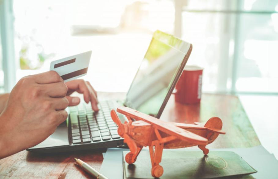 Imagem de uma mão segurando um cartão de crédito fazendo compras online para começar a juntar milhas aéreas no programa de fidelidade.