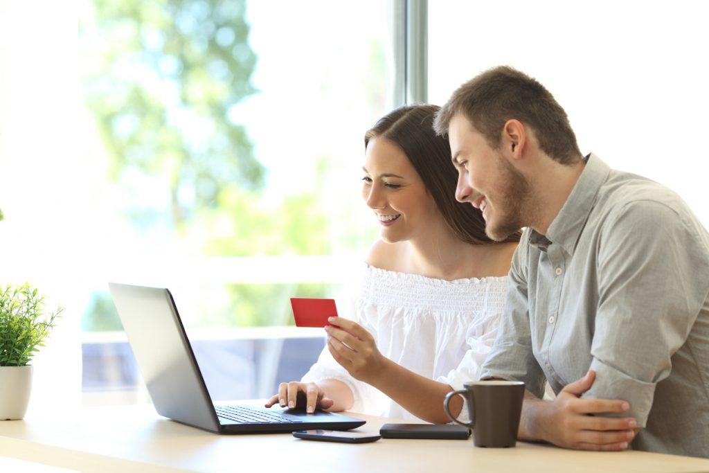 Casal sentado a frente do computador buscando parceiros de cartão de crédito com programas de pontos