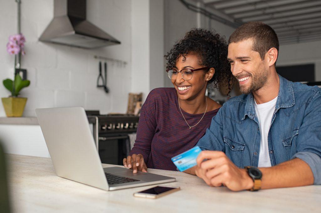 Casal sentado no computador buscando sites parceiros de pontos