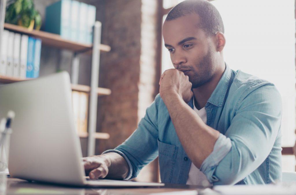 homem navegando no computador buscando informações sobre a venda de milhas