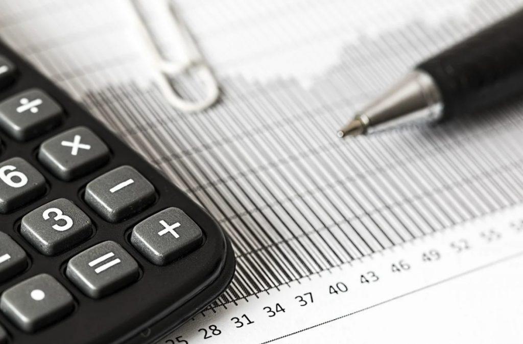 imagem de calculadora e caneta junto com planilhas para falar sobre a economia do setor aéreo