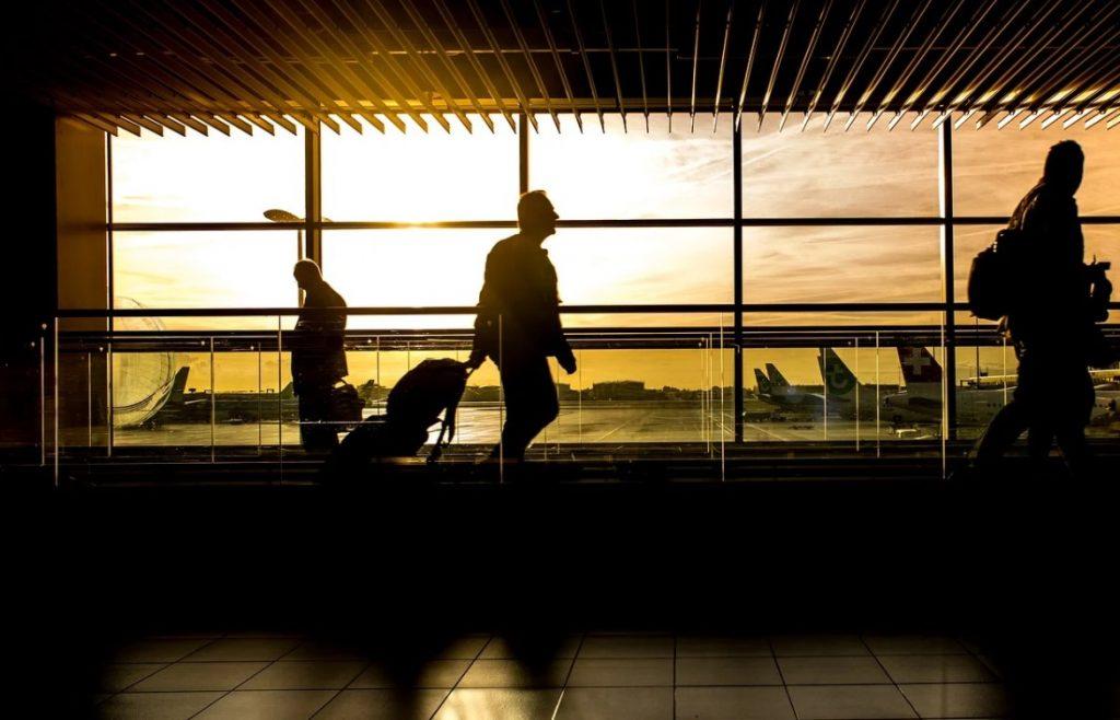 imagem de aeroporto no por do sol com os passageiros trafegando pelo saguão
