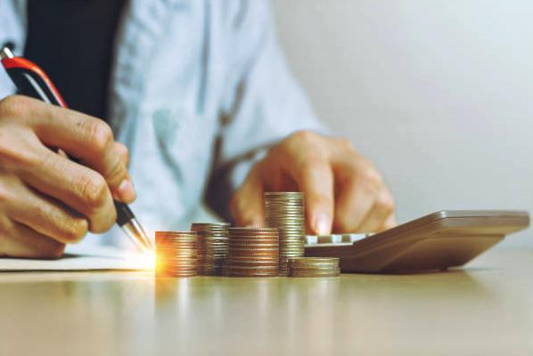 imagem de homem fazendo cálculos. Ao lado da calculadora, diversas pilhas de moedas