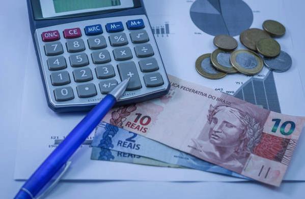 culadora, caneta e cédulas de dinheiro