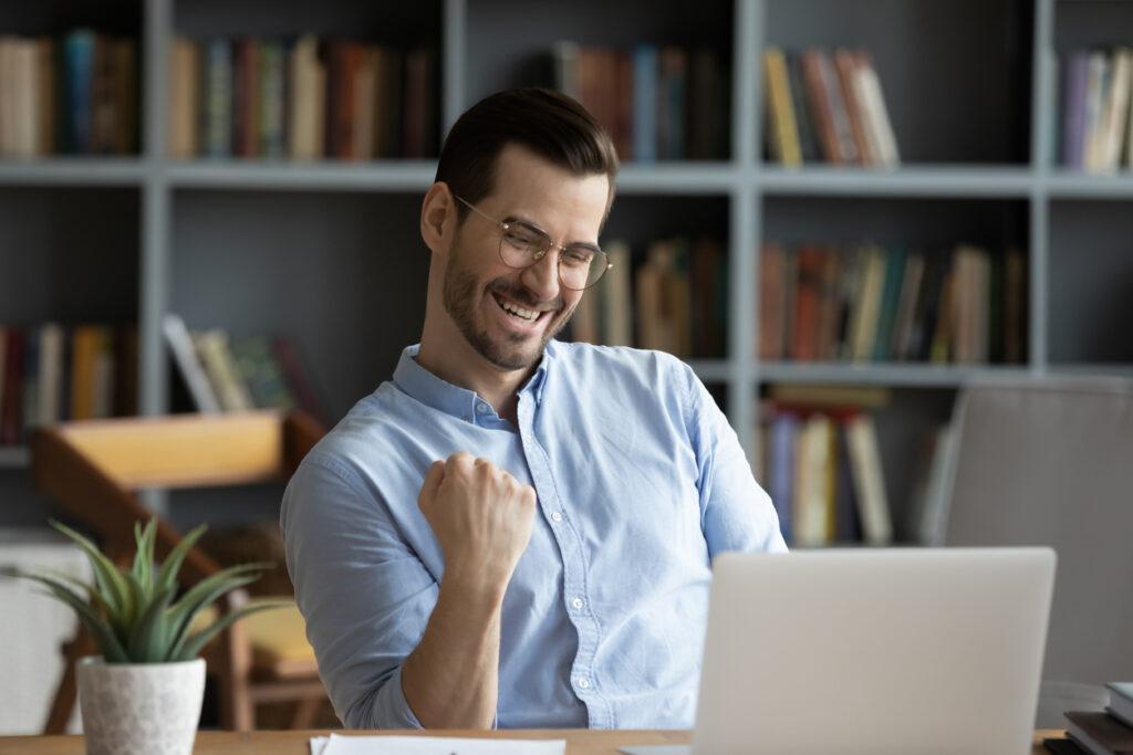Homem sentando no seu escritório comemorando ao descobrir benefícios de acumular pontos Livelo.