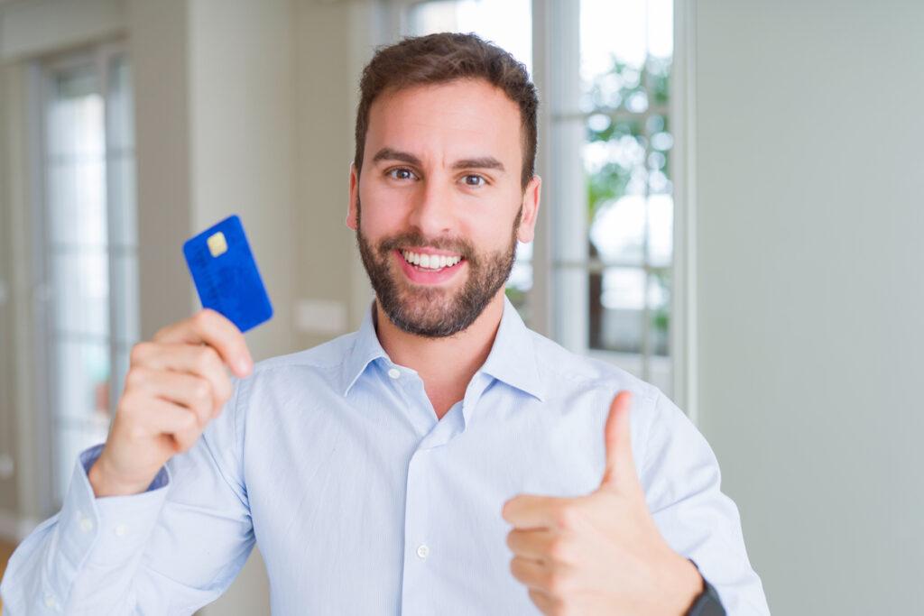 Homem feliz segurando o cartão de débito.