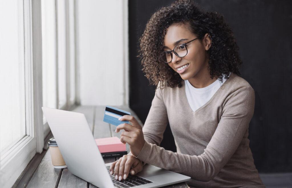 Jovem executiva segurando um cartão de crédito, utilizando o notebook para verificar em qual empresa encontra a melhor cotações de milhas para vendê-las.